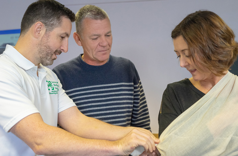 first aid trainer with students demonstrating application of sling